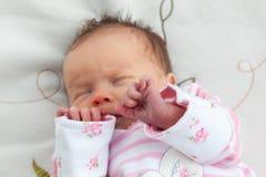 抓住她的手的新出生的女婴对她的面孔 免版税库存照片