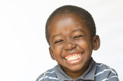 在非洲黑人种族黑色在白色画象隔绝的男孩孩子的令人敬畏的巨大的微笑 免版税库存照片