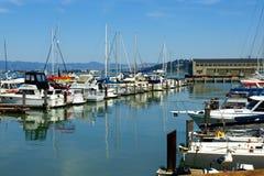 在靠码头的小船之间的平静的水 免版税库存照片