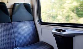 在靠窗座位的手机在一列现代舒适的火车 免版税库存图片