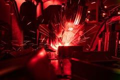 在面具焊接金属地道射击的焊工通过红色保险柜 库存图片