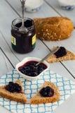 在面包切片的蓝莓果酱在木背景 图库摄影