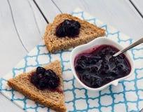 在面包切片的蓝莓果酱在木背景 库存照片