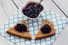 在面包切片的蓝莓果酱在木背景 库存图片