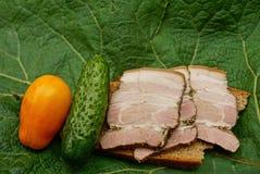 在面包和新鲜蔬菜的火腿在一片大绿色叶子 库存图片