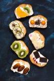 在面包多士的各种各样的果子与奶油 在土气背景的甜三明治 顶视图 图库摄影