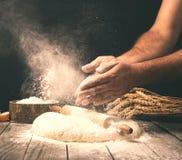 在面包店供以人员准备在木桌上的面团 免版税图库摄影