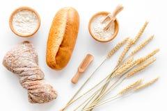 在面包店工作表背景顶视图的烘烤的新鲜的小麦面包 免版税库存图片