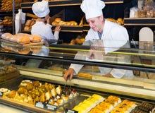 在面包店给提供的新鲜的长方形宝石和小圆面包雇用职员 免版税库存照片