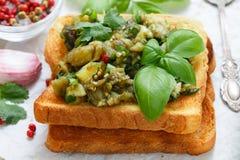 在面包油煎方型小面包片的被烘烤的茄子用大蒜、香菜和蓬蒿 辣的快餐 免版税库存照片