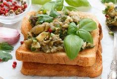 在面包油煎方型小面包片的被烘烤的茄子用大蒜、香菜和蓬蒿 辣的快餐 库存照片