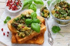 在面包油煎方型小面包片的被烘烤的茄子用大蒜、香菜和蓬蒿 辣的快餐 图库摄影