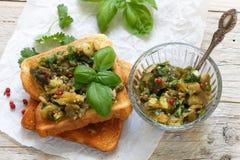 在面包油煎方型小面包片的被烘烤的茄子用大蒜、香菜和蓬蒿 辣的快餐 免版税库存图片