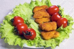 在面包渣的鸡nagets在绿色莴苣离开与蕃茄在一块白色板材 特写镜头 免版税库存图片