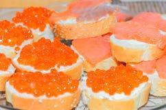在面包白色板材特写镜头的红色鱼子酱 免版税库存照片