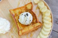 在面包的冰淇凌冠上与蜂蜜配菜鞭打了奶油和香蕉在木盘 库存图片