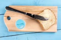 在面包的平的位置黄油传播与刀子和供食在一个木板 库存照片
