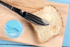 在面包的平的位置黄油传播与刀子和供食在一个木板 免版税库存照片