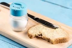 在面包的平的位置黄油传播与刀子和盐瓶在一个木板服务 库存照片