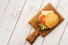 在面包的稀薄地切的辣蒜味咸腊肠鲜美开胃菜用乳酪、蕃茄和草本在一个切板有拷贝空间的 免版税库存照片