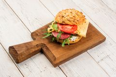 在面包的稀薄地切的辣蒜味咸腊肠鲜美开胃菜用乳酪、蕃茄和草本在一个切板有拷贝空间的 免版税图库摄影