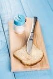 在面包的黄油传播与刀子和供食在一个木板 免版税库存图片