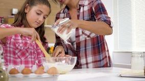 在面团的妇女倾吐的牛奶在厨房 股票视频