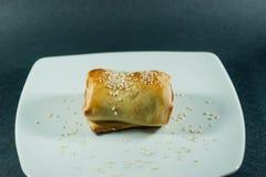 在面团的腊肠卷在一块白色板材 免版税库存图片