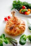 在面团的鸡腿用土豆、在烤箱和香料烘烤的蕃茄、葱 免版税库存图片