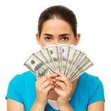 在面孔前面的妇女藏品被扇动的美元 免版税库存照片