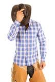 在面孔的牛仔蓝色格子花呢上衣举行帽子 免版税库存照片