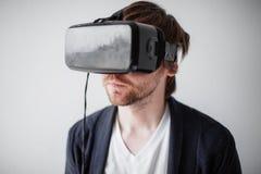在面孔的选择聚焦 戴虚拟现实眼镜的英俊的人隔绝了灰色背景 免版税库存照片