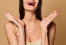 在面孔附近的女孩愉快地微笑的愉快的举行的手 免版税库存照片
