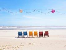 在面对海洋的一宽白色沙滩的五颜六色的海滩睡椅在有上面lampions和一条轻链的越南 免版税库存图片