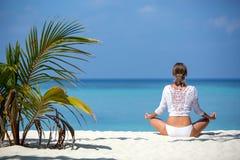 在面对海洋的海滩的少妇实践的瑜伽凝思在马尔代夫的一棵棕榈树附近 免版税库存照片