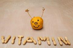 从在面带笑容前面的维生素药片创造的维生素标志 免版税库存图片