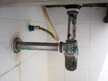 在面盆管子附近的绿色铁锈 肮脏和毒菌圆的管子 库存图片