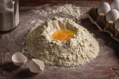 在面粉小山的残破的鸡蛋 库存照片