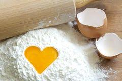 在面粉爱烘烤概念的卵黄质鸡蛋 图库摄影