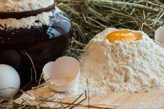 在面粉的卵黄质 残破的鸡蛋 白鸡蛋 在泥罐的面粉 库存图片