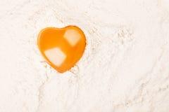 在面粉的心形的蛋黄 免版税库存图片