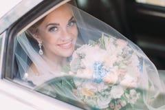 在面纱下的微笑的新娘拿着婚姻花束,当坐在汽车时 免版税库存照片