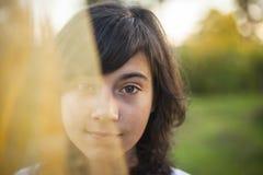 在面纱后掩藏的女孩画象半面孔 库存图片