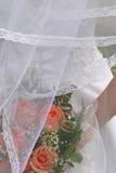 在面纱婚礼之下的花束 免版税库存图片