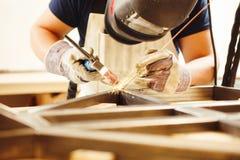 在面罩的男性焊接与氩弧焊接 免版税库存图片