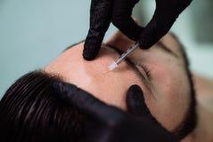在面部秀丽射入期间,关闭有注射器的男性耐心面孔和美容师` s手 Botox刺 图库摄影
