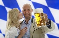 在面颊的巴法力亚慕尼黑啤酒节夫妇亲吻 图库摄影