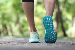 在鞋子、妇女跑在早晨的在公园,健身和健康生活方式概念的特写镜头 库存照片