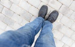 在鞋子的脚在路面 库存照片