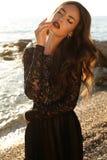 在鞋带摆在海滩的黑色礼服的美好的模型 免版税库存照片